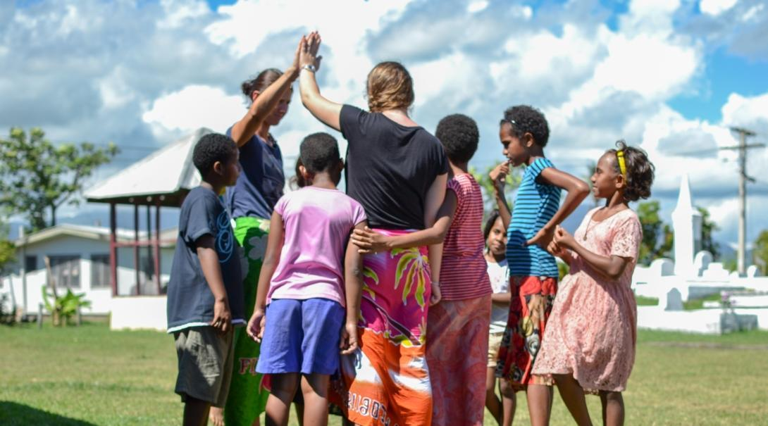 Teenagers doing volunteer work with children in Fiji lead an activity on the playground.